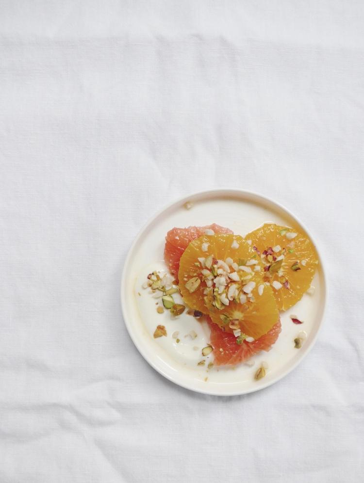 breakfast of oranges, yoghurt, pistachio and hazelnuts on allthatshecraves.com
